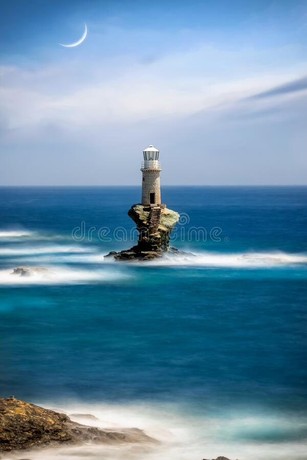 A lighthouse on a solid rock in the stormy sea as seen on Andros island royalty free stock photo
