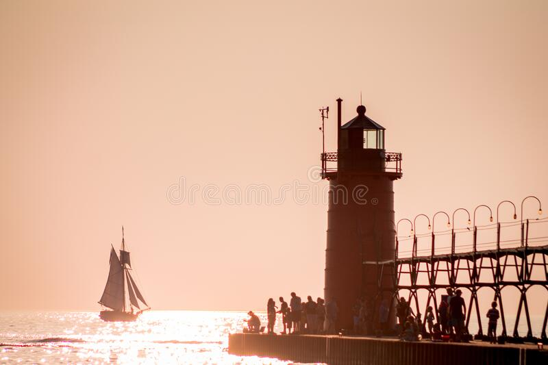 Lighthouse and tall ship at sunset. In Michigan stock images
