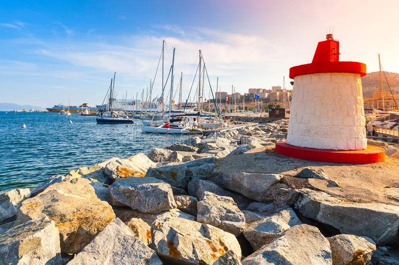 Lighthouse tower in a sunshine, Corsica, Ajaccio. Ajaccio marina entrance pier with red and white lighthouse tower in a sunshine, Corsica island, France stock images