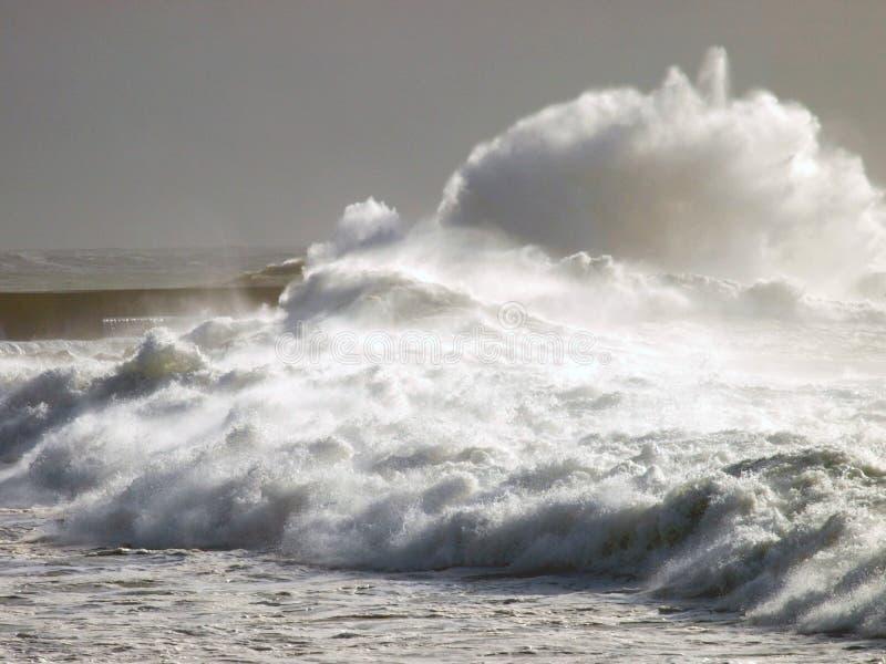 Lighthouse under big waves stock photography