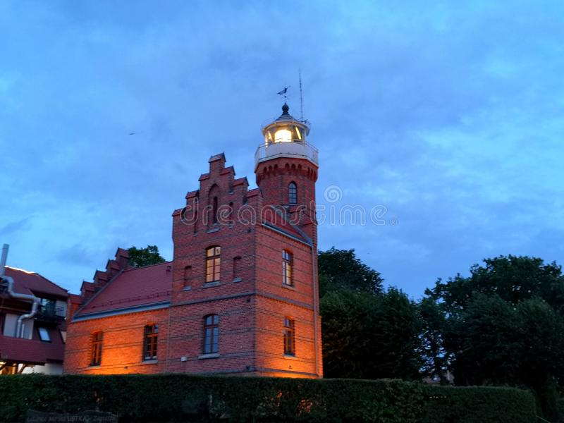 Lighthouse in Ustka, Poland. Travel, sea, shore, nighr, night, coast, sky, signal, architecture, monument, historic, buding, building, windows, facade, wall royalty free stock images