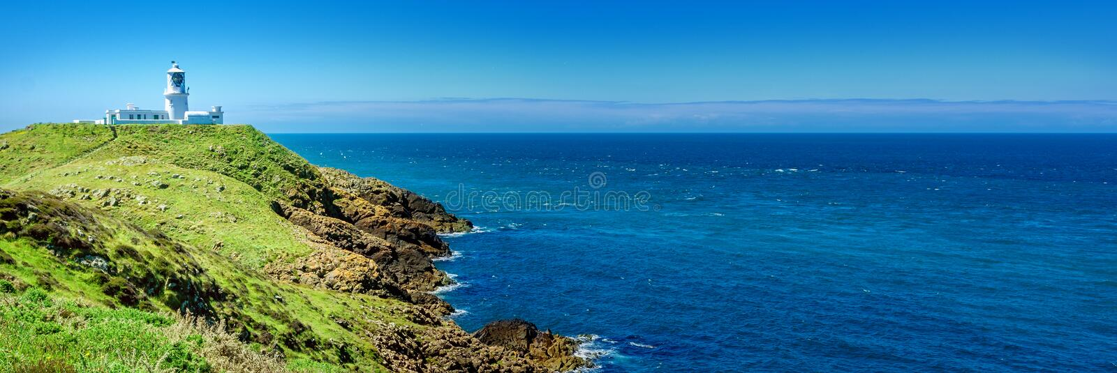 Lighthouse in Wales. Panorama: White lighthouse at the coast of South Wales stock photography