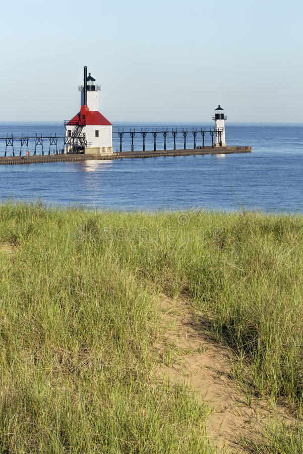 Lighthouses from the Dunes. The North Pier Inner and Outer Lighthouses at St. Joseph, Michigan are viewed from a trial in the dunes overlooking Lake Michigan stock images