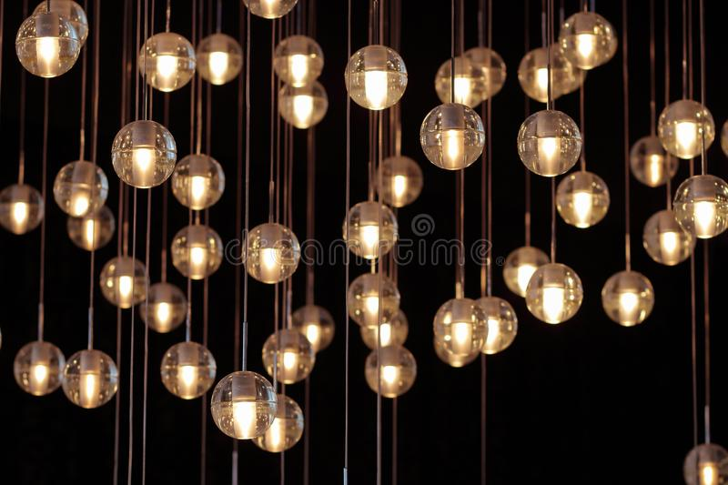 Lighting balls on the chandelier in the lamplight, light bulbs hanging from the ceiling, lamps on the dark background, selective. Focus, horizontal stock photos