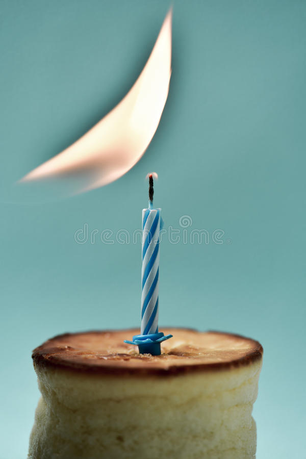 Lighting a birthday candle on a cheesecake stock photo