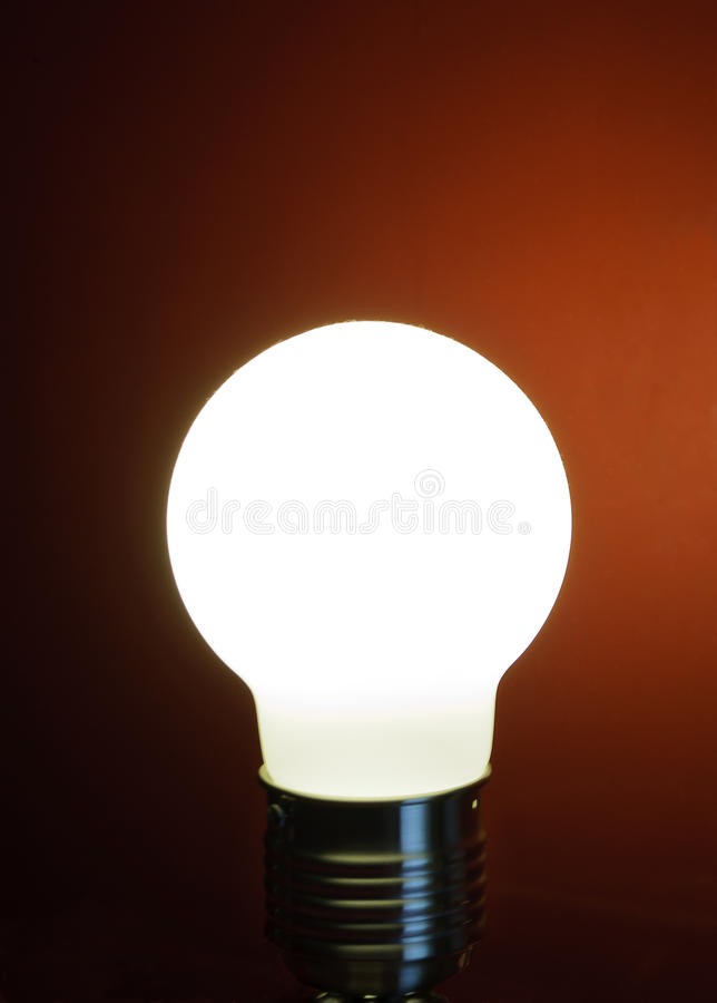 Lighting bulb. A lighted bulb on a dark red background, or simply an idea royalty free stock images