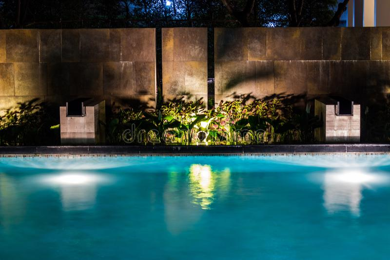 Lighting business for luxury backyard swimming pool. Relaxed lifestyle with contemporary design by professionals. Lighted plants and rock stone wall royalty free stock photos