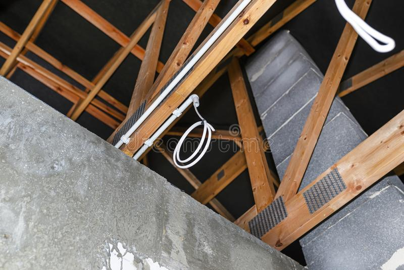 Lighting cables in plastic wiring pipes in a newly built house mounted on roof trusses. royalty free stock photo