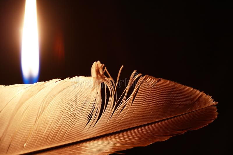Lighting Candle Near Feather stock photography