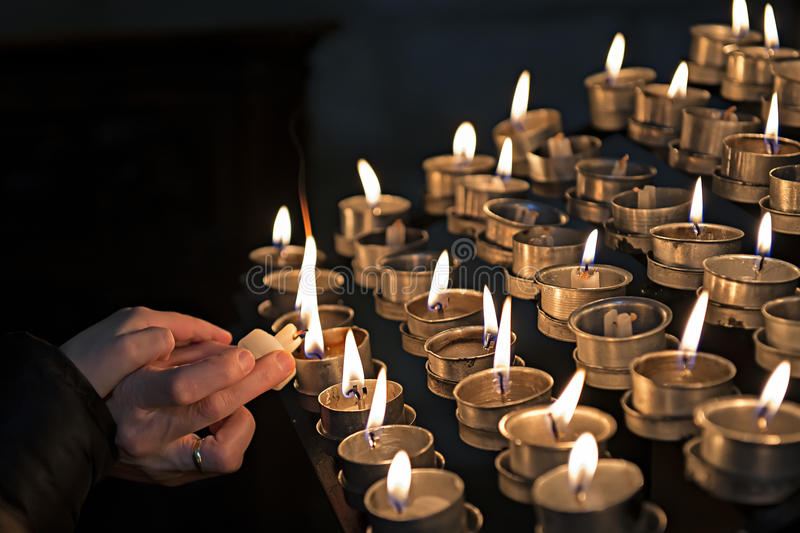 Lighting candles in a church. A womand lights candles in a church while her child put his hand on hers royalty free stock image