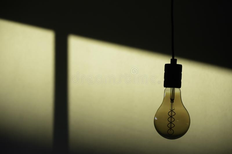 Lighting decor. Transparent hanging decor retro light bulb on empty wall with light from window royalty free stock photo