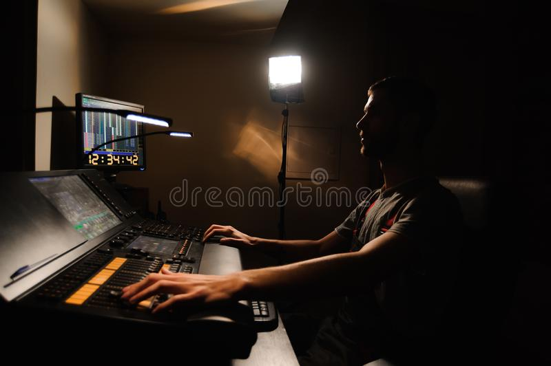 A lighting engineer works with lights technicians control on the concert show. Professional light mixer, mixing console. Equipment for concerts royalty free stock images