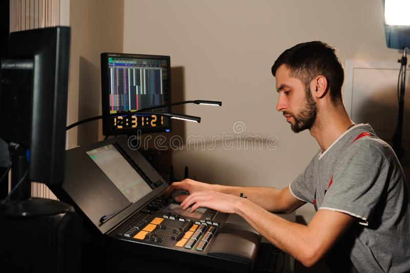 A lighting engineer works with lights technicians control on the concert show. Professional light mixer, mixing console. Equipment for concerts stock image