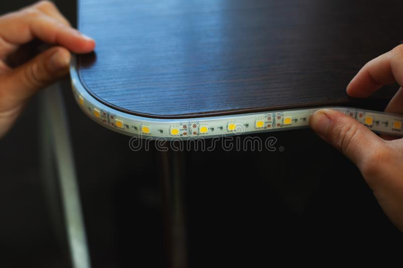 Lighting install,the master makes the installation of LED strip on the upper niches of the cabinet at home. Close-up royalty free stock images