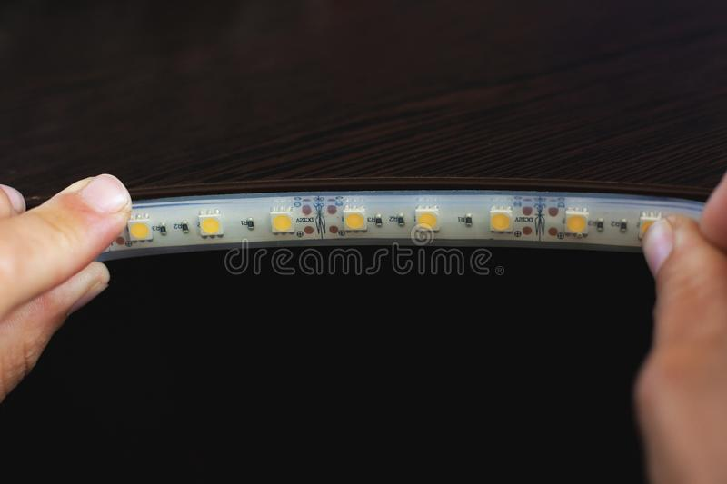 Lighting install,the master makes the installation of LED strip on the upper niches of the cabinet at home. Close-up royalty free stock photo