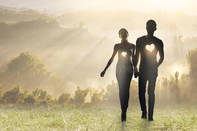 Lighting love. Silhouette of Asian couple hold hands walking on grassland royalty free stock photography