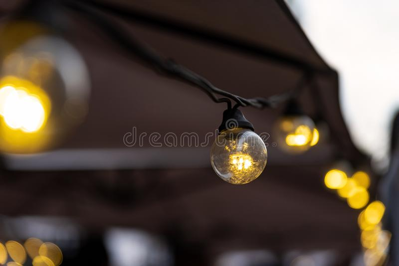 Lighting from small light bulbs in a summer cafe. Small light bulbs in a summer cafe stock images