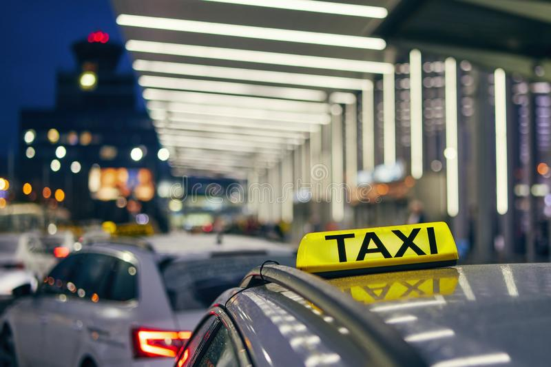 Lighting taxi sign. On the roof of car against airport terminal at night stock photos