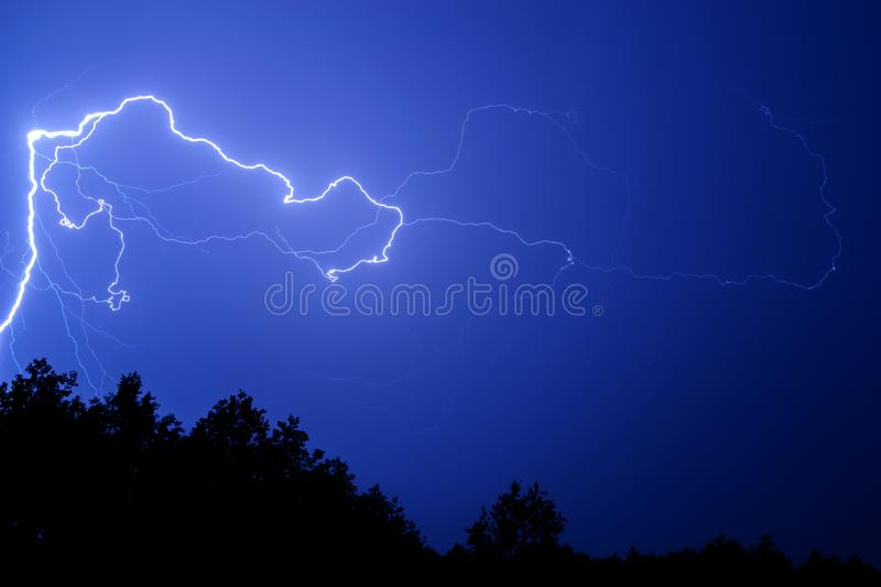 Lightning against a blue night sky above the trees. Bright lightning on a blue sky at night over the trees stock photography