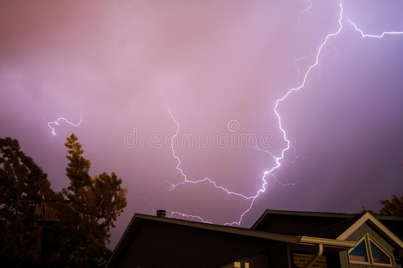 Lightning Bolt Above a House. A lightning bolt flashes above a house and tree royalty free stock photos