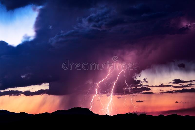 Lightning bolts strike from a storm at sunset. Lightning bolts strike from a storm with dramatic clouds and colorful, sunset sky royalty free stock photos
