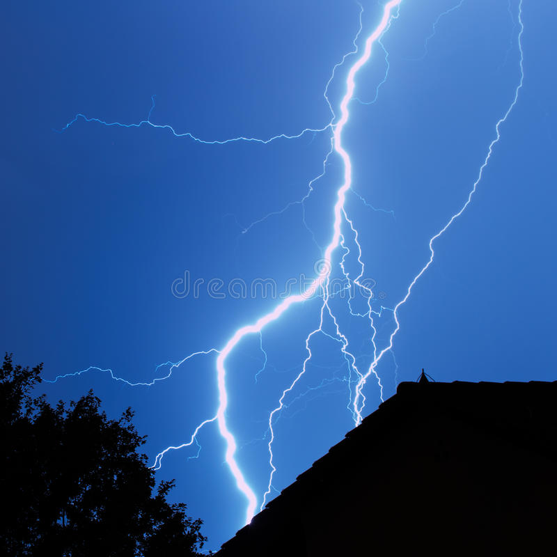 Lightning in the city. Thunderbolt with house and tree stock photography