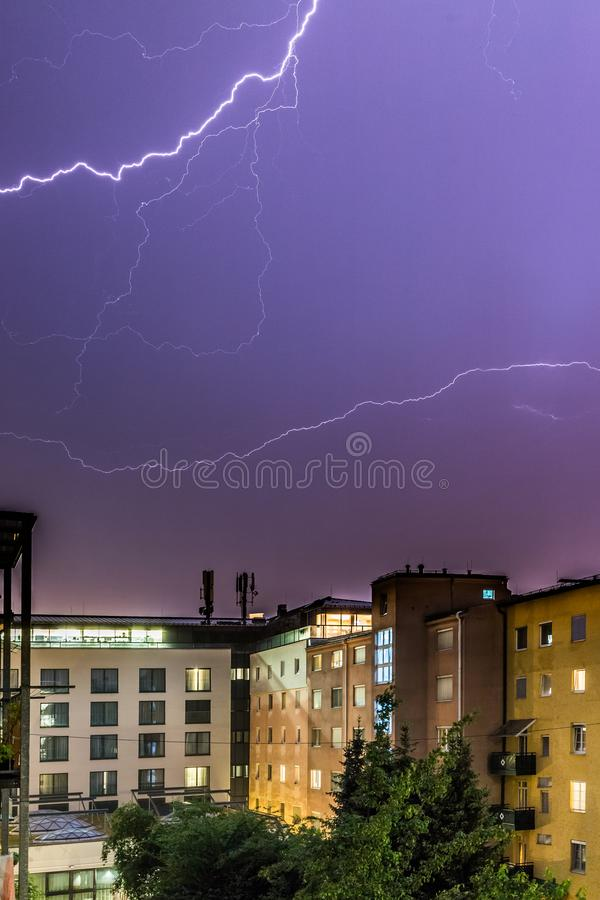 Lightning on the cloudy sky, urban city life with buildings, Austria. Thunderstorm in the night: Lightning on the sky, urban city, Austria, energy, electricity stock photo