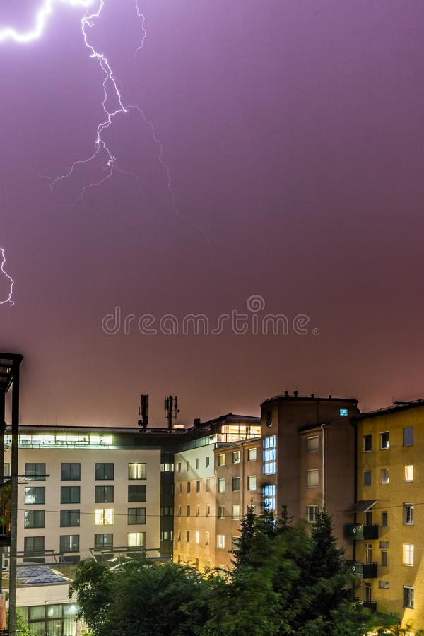 Lightning on the cloudy sky, urban city life with buildings, Austria. Thunderstorm in the night: Lightning on the sky, urban city, Austria, energy, electricity royalty free stock photos