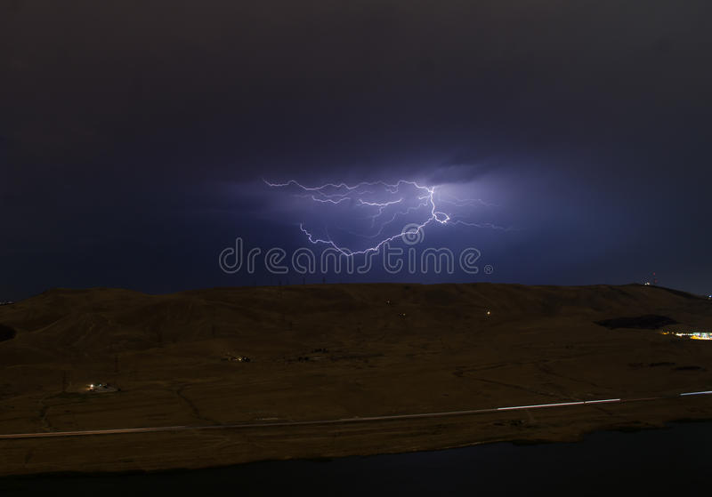 Lightning with dramatic clouds. Night thunder-storm over the mountain and the lake in Baku, Azerbaijan stock image