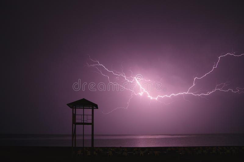 Lightning flashes across the night sky on beach. Violet color. Weather concept in resort areas.  royalty free stock images