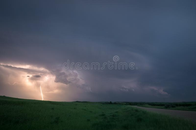 Lightning from a supercell thunderstorm over the northern plains, USA during blue hour. Lightning flashes to the ground from a supercell thunderstorm over the stock photos
