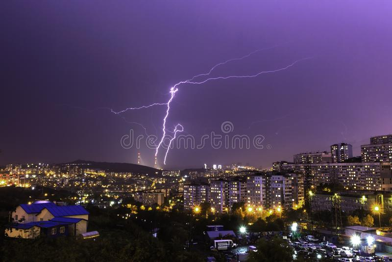 Lightning hitting the bridge during a purple sunset in the city stock photography