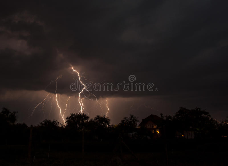 Storm. Lightnings and heavy storm clouds over village profile houses stock images