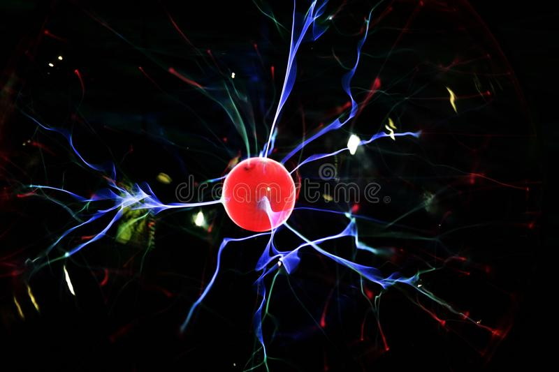 Lightning meeting electrode in the plasma lamp, glowing red stock photography