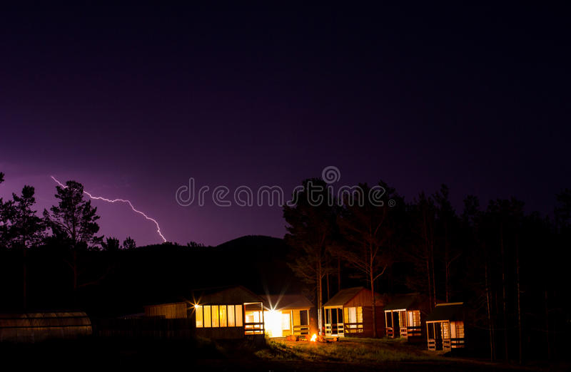Lightning in the night sky over houses royalty free stock photo