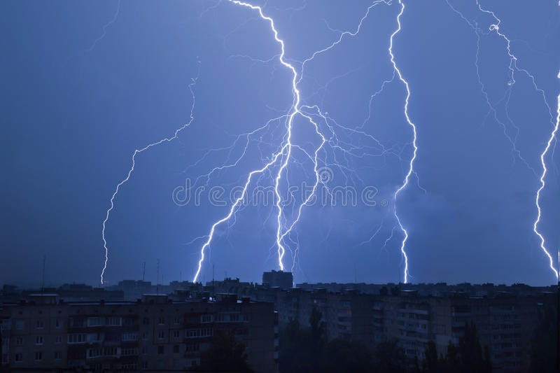 Lightning over the city in the night sky strikes the roof of the house royalty free stock images