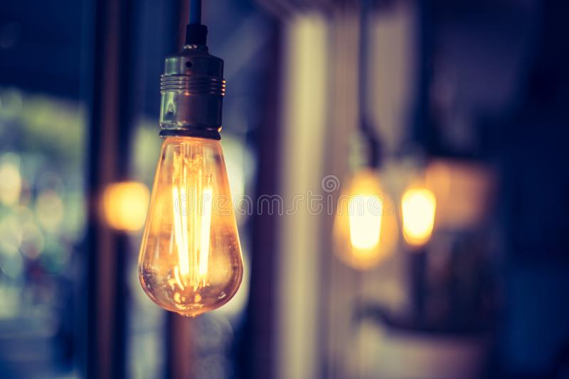 Lightning in the restaurant: Close up of a hanging, orange lightbulb. Close up picture of a hanging orange lightbulb in a restaurant or caf idea illumination stock images