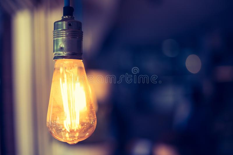 Lightning in the restaurant: Close up of a hanging, orange lightbulb. Close up picture of a hanging orange lightbulb in a restaurant or caf idea illumination stock image