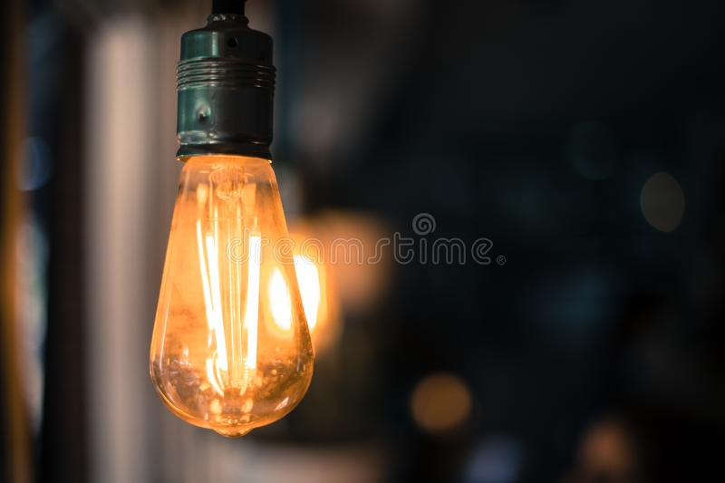 Lightning in the restaurant: Close up of a hanging, orange lightbulb. Close up picture of a hanging orange lightbulb in a restaurant or caf idea illumination royalty free stock image
