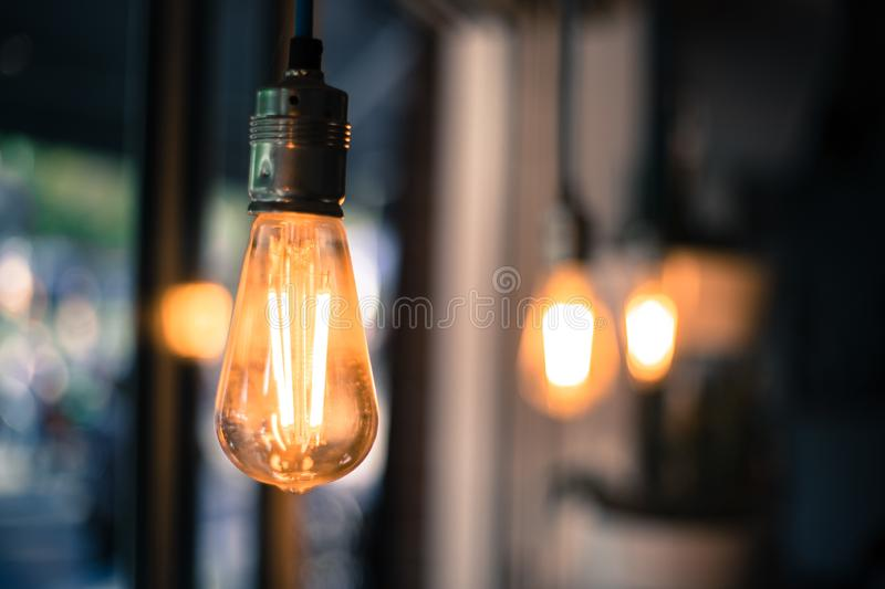 Lightning in the restaurant: Close up of a hanging, orange lightbulb. Close up picture of a hanging orange lightbulb in a restaurant or caf idea illumination royalty free stock photography