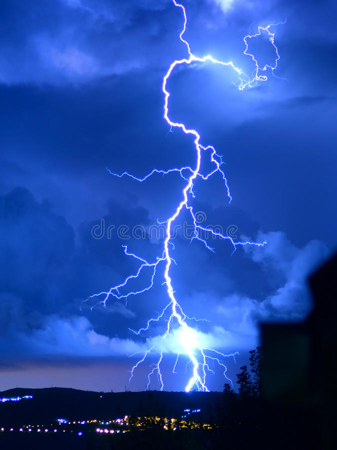 Lightning storm. Beautiful lightning that comes down from the clouds to the land and brightens the sky day royalty free stock images
