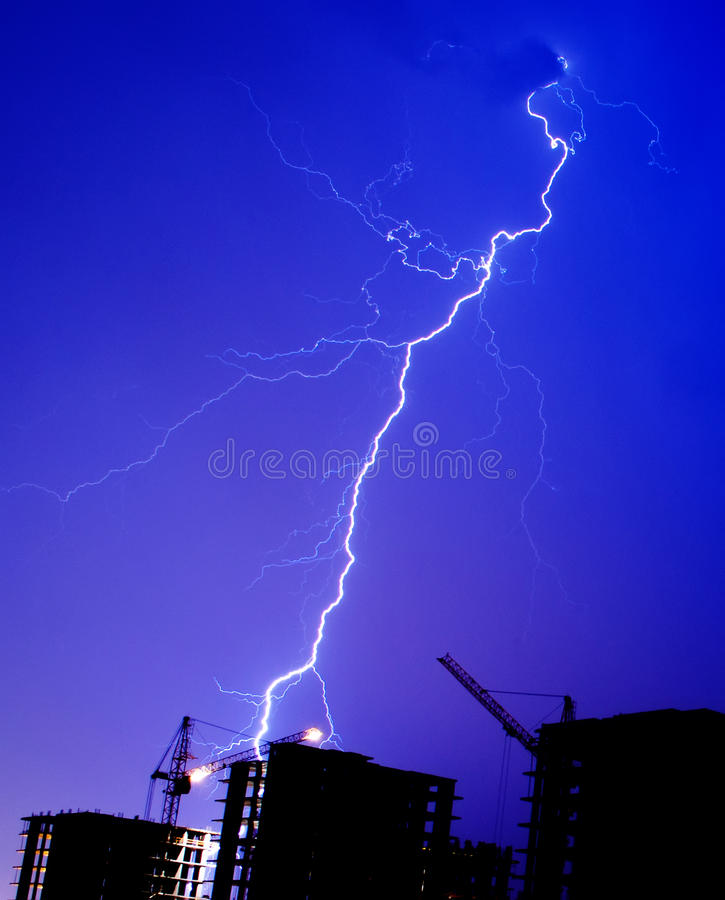 Lightning storm crane weather industrial city building construction night flash royalty free stock photography