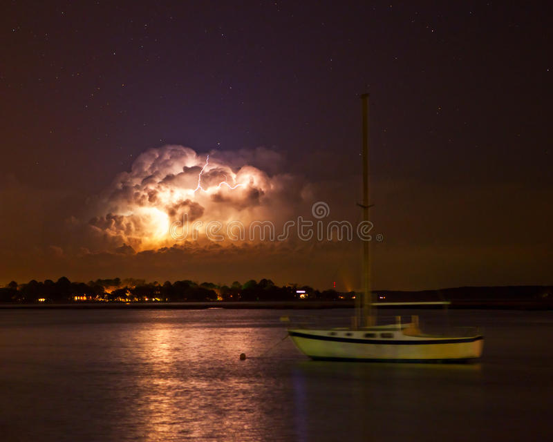 Lightning storm at night. Lightning storm over water at night stock photo