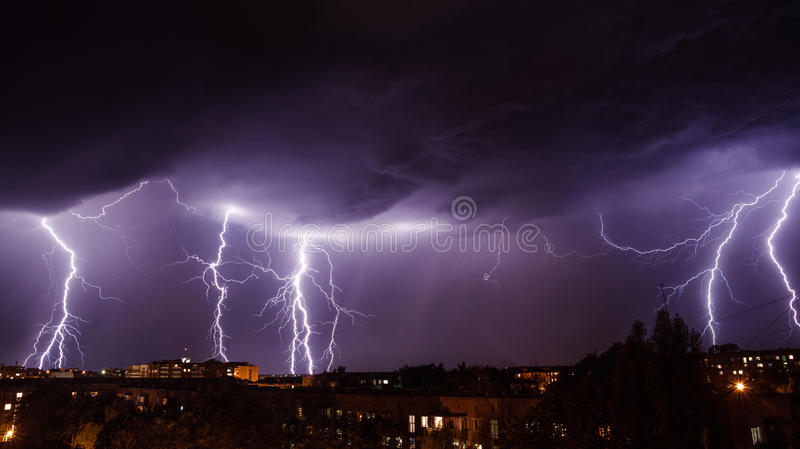 Lightning storm over city. In purple light stock images