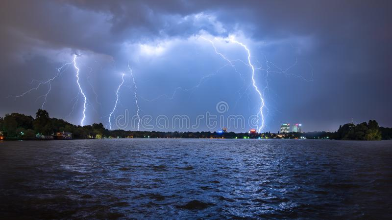 Lightning storm over the city in summer time Romania heavy rain. Bucharest sky line with lightning storm over the city in summer time Romania heavy rain with stock photography