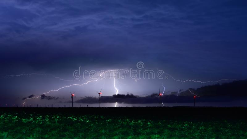 Lightning storm over windmill eolian park in Romania stock photography