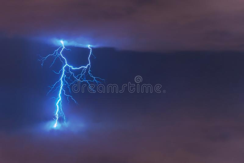 Lightning strike flash, electric discharge between clouds at night royalty free stock photography