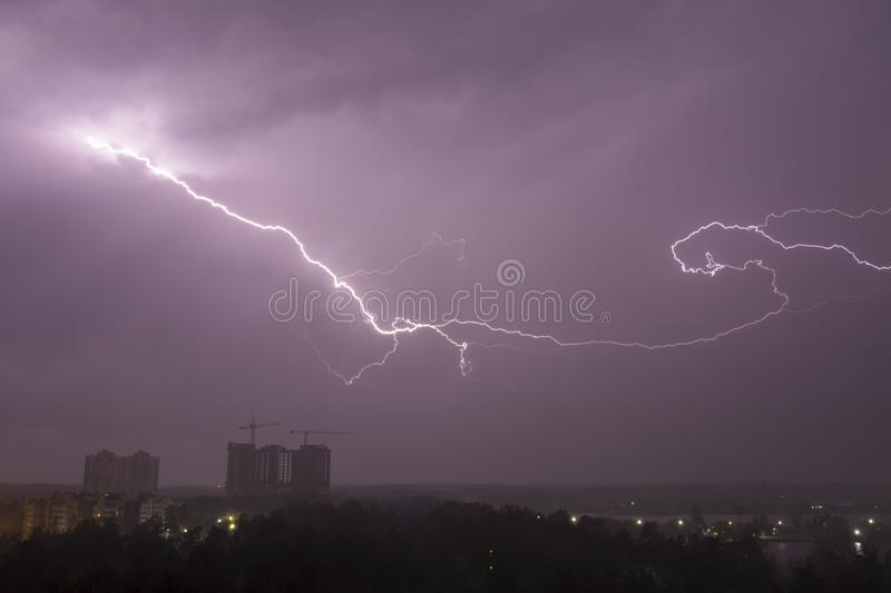 Lightning strike over city in night. Thunderstorm royalty free stock image