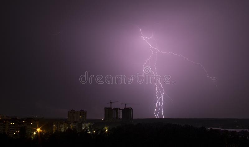 Lightning strike over city in night. Thunderstorm stock photo