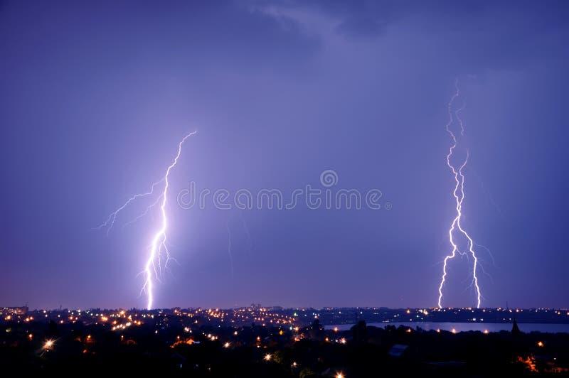 Lightning strike over dark blue sky in night city royalty free stock photo